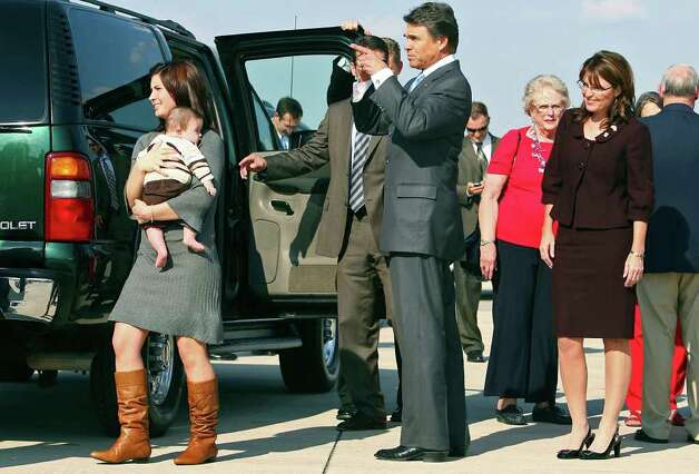 Gov. Rick Perry directs Willow Palin who is carrying infant Trig Palin to vehicles as Republican vice presidential candidate and Alaska Gov. Sarah Palin (right) arrives at San Antonio International Airport, Oct. 3, 2008. Photo: Tom Reel, AP / San Antonio Express-News