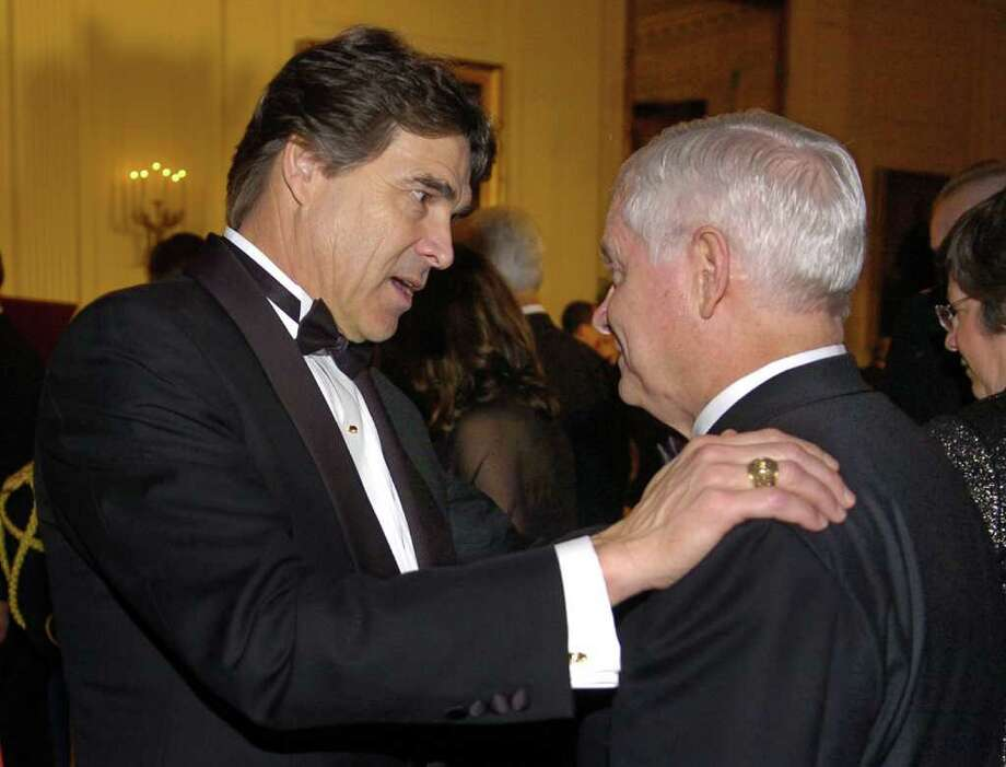 Texas Governor Rick Perry chats with Defense Secretary Robert M. Gates on arrival in the East Room for a dinner at the White House, Feb. 25, 2007, in Washington. President George W. Bush held a State Dinner at the White House in honor of the nation's governors.  Photo: Pool, Getty Images / 2007 Getty Images
