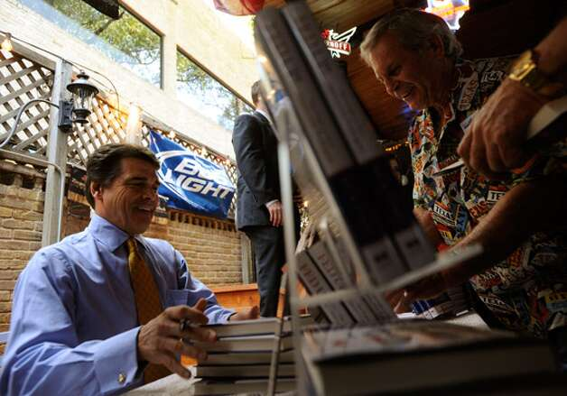 "Gov. Rick Perry signs copies of his book ""Fed Up! Our Fight to Save America from Washington"" at Augie's Barbed Wire Smokehouse Bar-B-Que near Brackenridge Park."