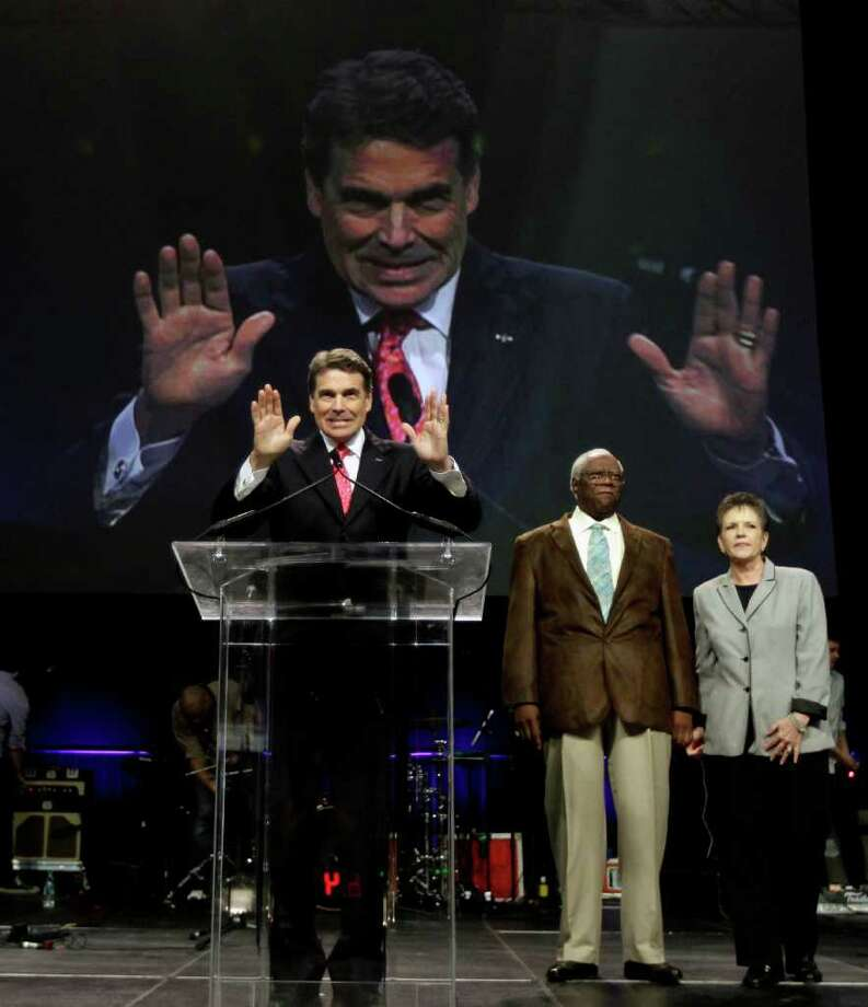 Texas Gov. Rick Perry acknowledges the crowd at The Response, Aug. 6, 2011, in Houston. Perry attended the daylong prayer rally despite criticism that the event inappropriately mixes religion and politics. Photo: AP