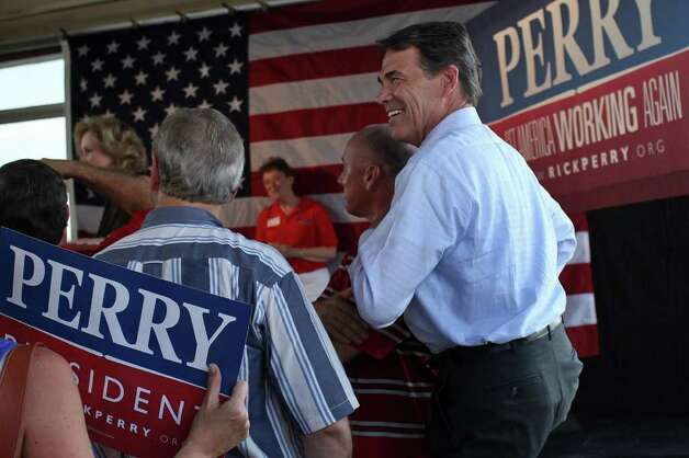 Governor Rick Perry takes in the applause as his wife, Anita, introduces him upon their arrival at the Rick Perry Welcome Home Rally at Abel's on the Lake in Austin, Aug. 20, 2011. Photo: LISA KRANTZ, Express-News / SAN ANTONIO EXPRESS-NEWS