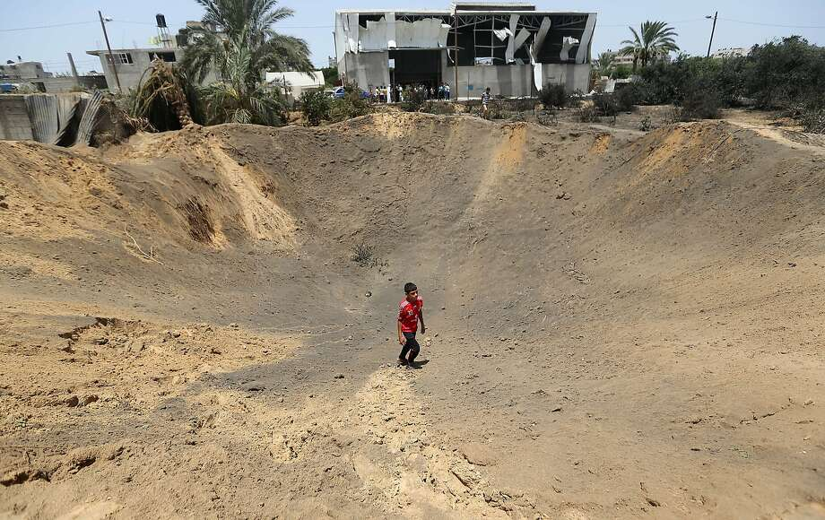 A Palestinian youth walks inside a crater left by an Israeli airstrike  