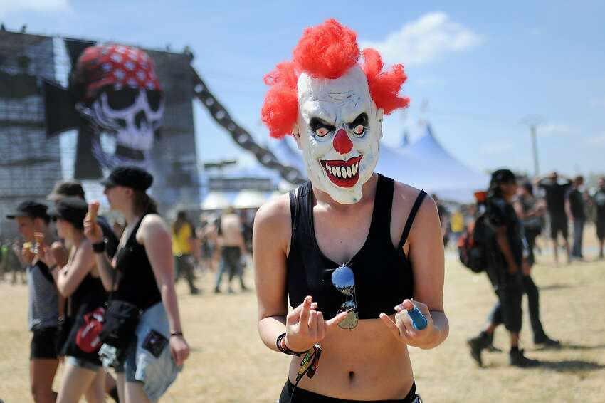 Her hand says come hither, but her face says run away: A heavy metal fan clowns around at the Hellfest Heavy Music Festival in Clisson, France.
