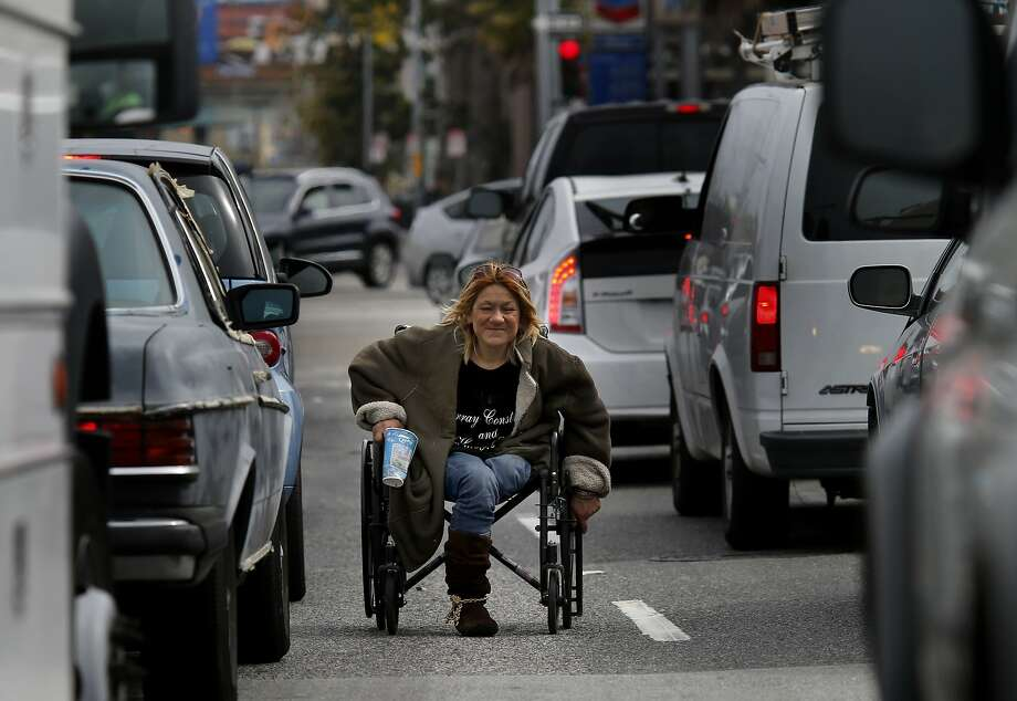 """Vina Villegas takes her wheelchair into traffic to panhandle from passing commuters last year. Villegas used to sleep on a traffic median at South Van Ness Avenue and Mission Street that its inhabitants called """"Homeless Island"""" before they were dispersed. Photo: Brant Ward, The Chronicle"""