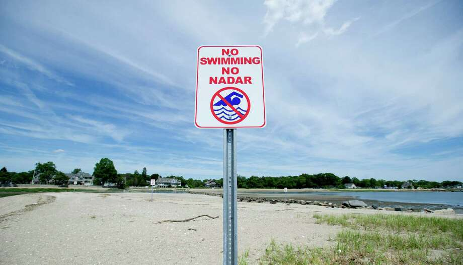 Signs warning visitors not to swim near the Holly Pond dam, where Rahad Gross drowned last year, stand at Cove Island Park in Stamford, Conn., on Friday, June 20, 2014. Photo: Lindsay Perry / Stamford Advocate