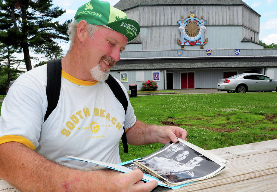 Ed Goodrich, Chairman of the Stratford Arts Commission, goes through some photos depicting some of the past actors and actresses that have performed at Shakespeare Theater, in background, in Stratford, Conn. on Thursday June 19, 2014. Photo: Christian Abraham / Connecticut Post