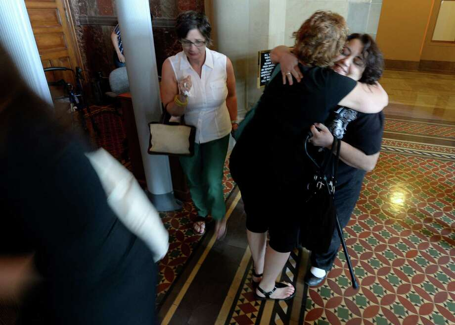 Medical marijuana advocates hug and share cry Friday afternoon, June 20, 2014, after the Medical Marijuana bill passed by the State Senate at the Capitol in Albany, N.Y. (Skip Dickstein / Times Union) Photo: SKIP DICKSTEIN / 00027457A