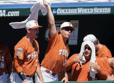 Players in the Texas dugout celebrate after Ben Johnson scored against Vanderbilt in the first inning of an NCAA baseball College World Series game in Omaha, Neb., Friday, June 20, 2014. (AP Photo/Nati Harnik) Photo: Nati Harnik, Associated Press / AP