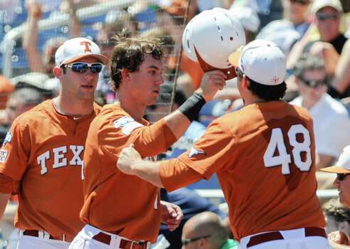 Texas' Ben Johnson, center, is greeted at the dugout by Ty Marlow (48) and catcher Jacob Felts, left, after scoring against Vanderbilt in an NCAA baseball College World Series game in Omaha, Neb., Friday, June 20, 2014. (AP Photo/Eric Francis) Photo: Eric Francis, Associated Press / FR9944 AP
