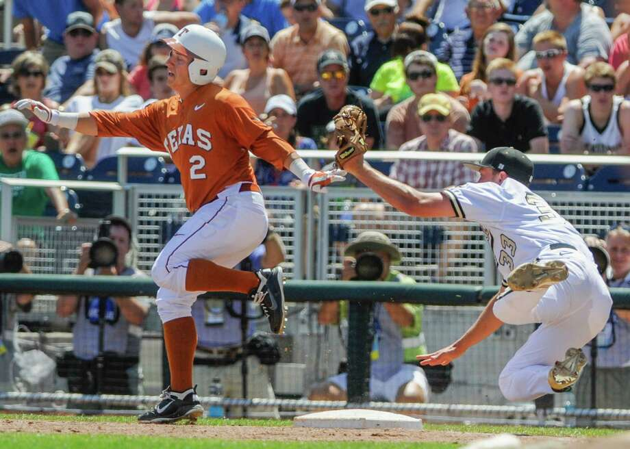 Texas' Mark Payton, left, is safe at first base after Texas pitcher Dillon Peters, right, stumbled and dropped the ball following the tag in the inning of an NCAA baseball College World Series game in Omaha, Neb., Friday, June 20, 2014. (AP Photo/Eric Francis) Photo: Eric Francis, Associated Press / FR9944 AP