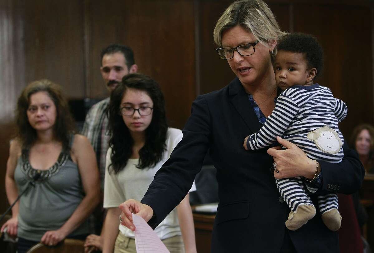 Assistant DA Teresa Drenick holds Jaydon Anderson while moving to dismiss a truancy case against Britnee Medrano (center), 15, and her family in Judge Gloria Rhynes' courtroom at the Alameda County courthouse in Oakland, Calif. on Friday, June 20, 2014.