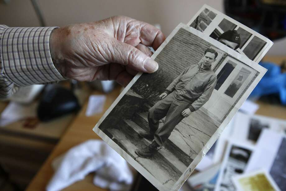 Ed Holton holds photos of himself during his service days. He was one of the Ritchie Boys, a group of Jewish refugees trained to interrogate Nazis. Photo: Michael Short, The Chronicle