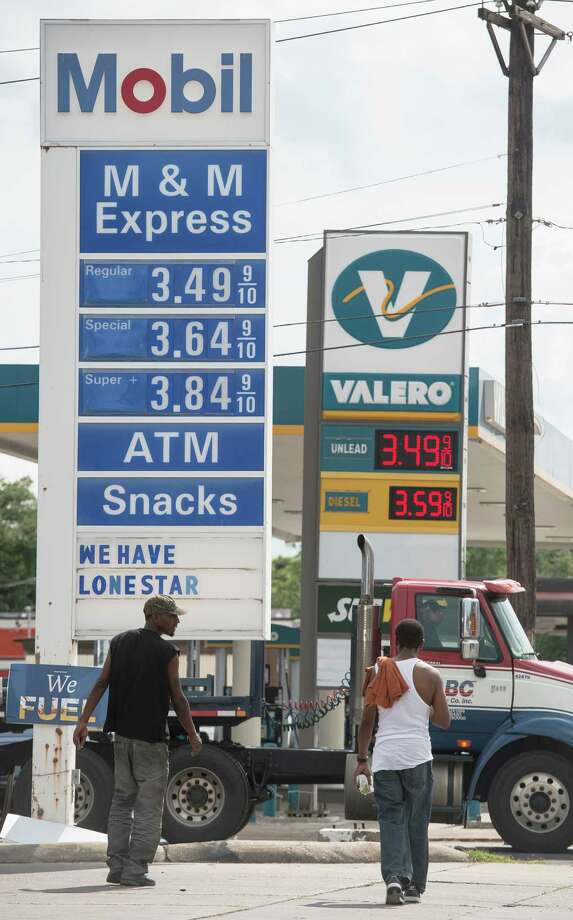 Men walk by gas stations on Washington Avenue on Friday. Gas stations along Washington Avenue advertise their prices Friday afternoon. Photo taken Friday 6/20/14 Jake Daniels/@JakeD_in_SETX Photo: Jake Daniels / ©2014 The Beaumont Enterprise/Jake Daniels