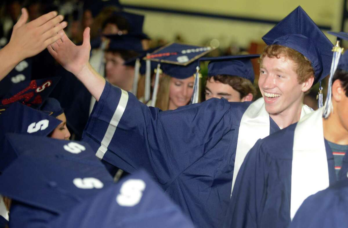 Graduate Alex Mapley high-fives a friend during the Staples High School commencement ceremony Friday, June 20, 2014 at the school in Westport, Conn.