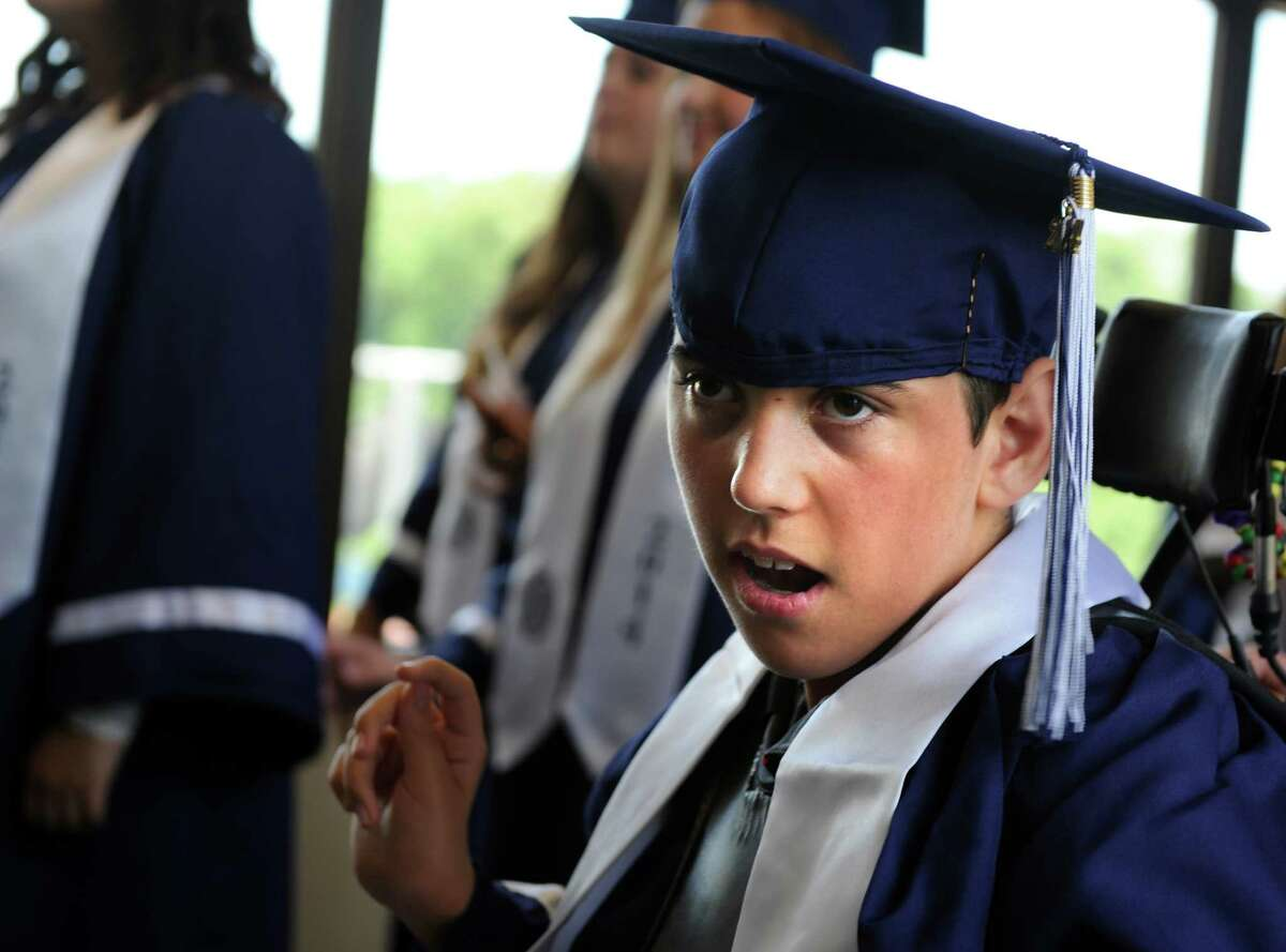 Graduate Wyatt Davis waits with his classmates for the start of the Staples High School commencement ceremony Friday, June 20, 2014 at the school in Westport, Conn.