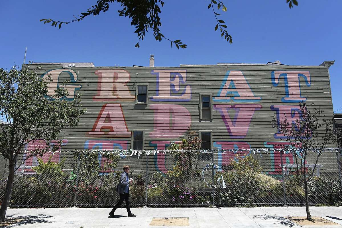 A man walks past the community garden which has been sold off to a developer on Octavia Blvd. in San Francisco, Calif. on Friday, June 20, 2014. Three lots along Octavia Boulevard have been awarded to development sites, two of which are community gardens.