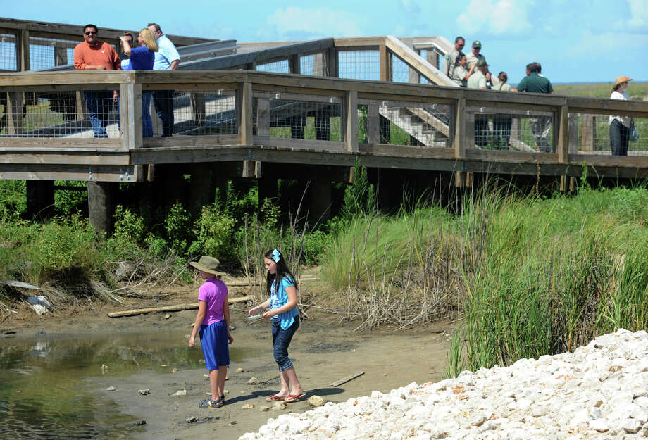 Guests walk along the newly opened pathway connecting the parking lot to the beach at Sea Rim State Park on Friday.   Photo taken Friday, June 20, 2014 Guiseppe Barranco/@spotnewsshooter Photo: Guiseppe Barranco, Photo Editor