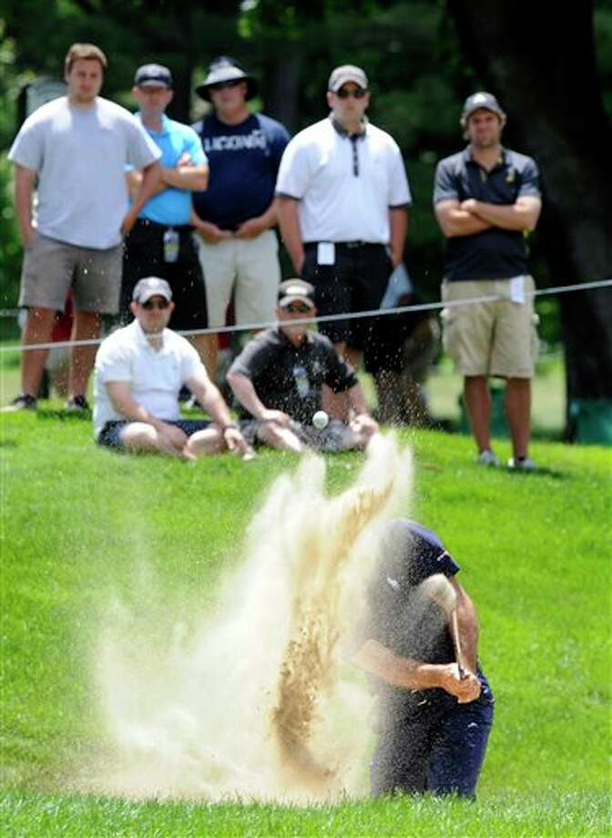 The crowd looks on as Jonathan Byrd hits out of a greenside bunker on the seventh hole during the second round of the Travelers Championship golf tournament in Cromwell, Conn., Friday, June 20, 2014. (AP Photo/Fred