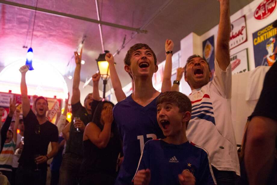 French soccer fans (clockwise from top right Zaf Diab, and his sons Dany and Sam) watch the France vs. Switzerland first round World Cup match at Cafe Bastille in San Francisco, CA.   The Diab's now live in Santa Clara and are going to travel to the Brazil for the World Cup. Photo: Douglas Zimmerman, Courtesy