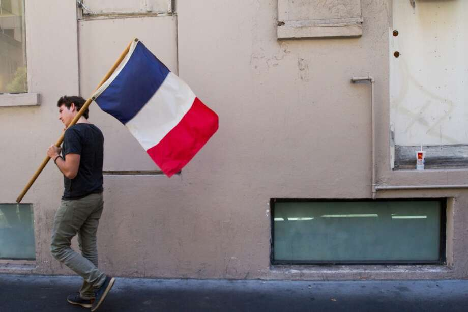 French-American soccer fan Louis-Pierre Guidetti of Mill Valley carries a France flag after watching the France vs. Switzerland first round World Cup match at Cafe Bastille in San Francisco, CA. Photo: Douglas Zimmerman, Courtesy