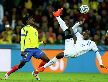 Honduras' Juan Montes, right, bicycle kicks the ball away from Ecuador's Juan Paredes during the group E World Cup soccer match between Honduras and Ecuador at the Arena da Baixada in Curitiba, Brazil, Friday, June 20, 2014. (AP Photo/Jon Super) Photo: Jon Super, Associated Press / AP