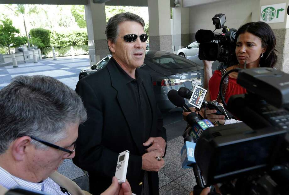 FILE - In this June 10, 2014 file photo, Texas Gov. Rick Perry, center, talks to reporters after driving up in a Tesla Motors Type S electric car in Sacramento, Calif. On Thursday, June 19, 2014, Perry said it was a mistake for him to recently compare alcoholism and homosexuality in an effort to explain his views. (AP Photo/Rich Pedroncelli, File) Photo: Rich Pedroncelli, STF / AP