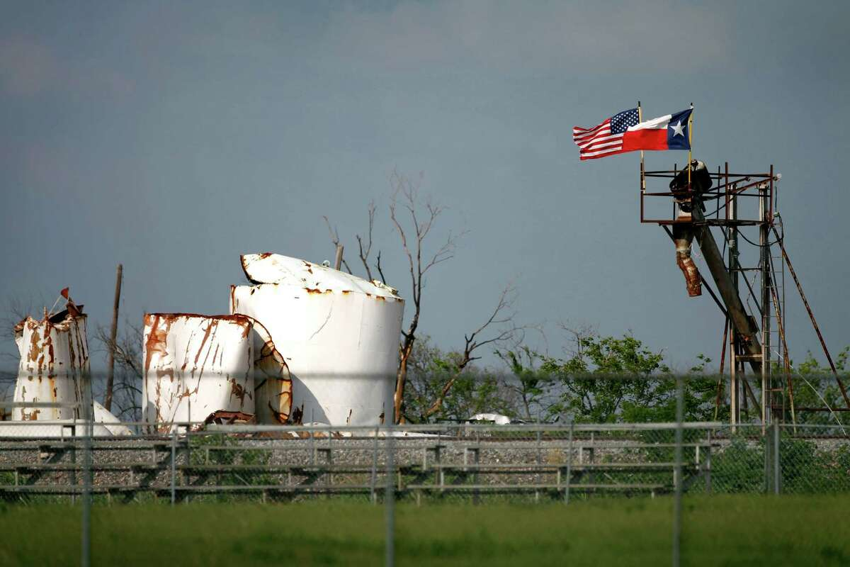 An American and Texas flag fly side by side Friday, May 31, 2013, in West, Texas, atop the destroyed remains of the fertilizer plant that exploded almost two months ago killing 15 and injuring 200. (AP Photo/Tony Gutierrez)