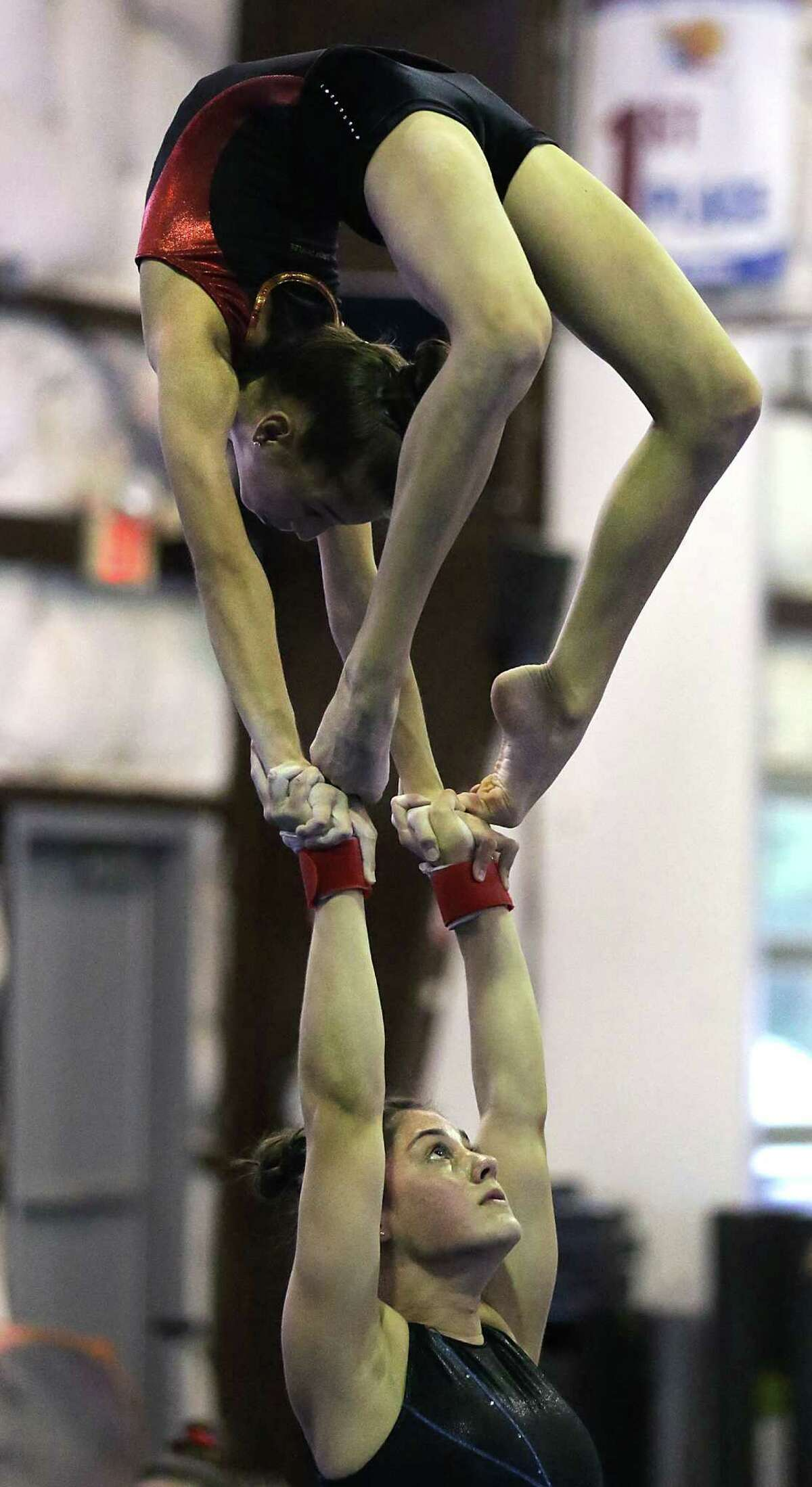 Kathleen Davis holds Katerina Partalas above her head as the two practice their routine at Acrobatic Gymnastics San Antonio. A team of young gymnasts will travel to Paris, France to compete in the Acrobatic Gymnastics World Championships. Friday, June 20, 2014.