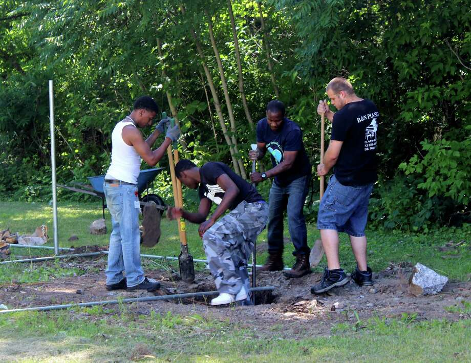 From left to right: Charles McFadden, 25, Marvin Payne, 18, Youth Support Specialist Tafari Harper, and Chris Peabody, 23, from Troy Youthbuild construct an outside shelter for dogs on Friday, June 20, 2014, at the Mohawk-Hudson Humane Society in Menands N.Y. (Selby Smith / Special to the Times Union) Photo: Selby Smith / 00027426A