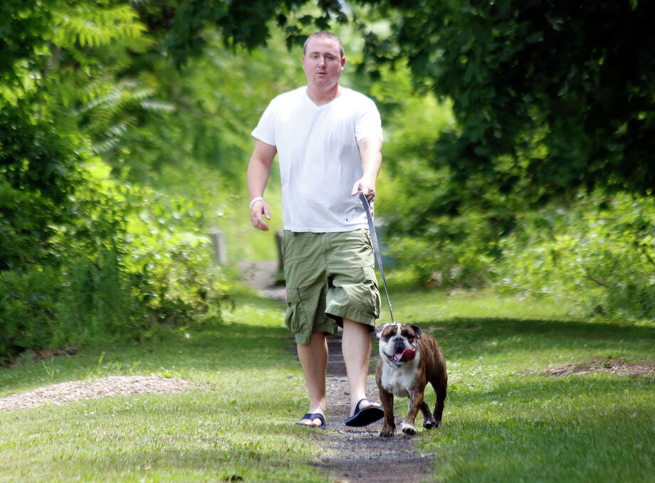 Patrick Gray of Delmar, walks his dog along the Rail Trail in Delmar, N.Y. on Wednesday, June 18, 2014.  The Rail Trail is a pedestrian public pathway that was converted from previous railroad lines that once ran into the city of Albany.  (Tom Brenner/ Special to the Times Union)     ORG XMIT: 00027390A Photo: Tom Brenner / ©Tom Brenner/ Albany Times Union