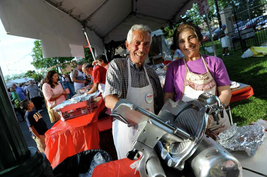 Church members Felice DiCocco, center, and his wife, Santina DiCocco, slice prosciutto for sandwiches during St. Anthony's Festa on Friday, June 20, 2014, in Schenectady, N.Y. The festival, featuring food, music and games, continues on Saturday from 3 to 11 p.m. and on Sunday, beginning with a tri-lingual mass at 1 p.m., with the festival following until 8 p.m. (Cindy Schultz / Times Union) Photo: Cindy Schultz / 00027428A