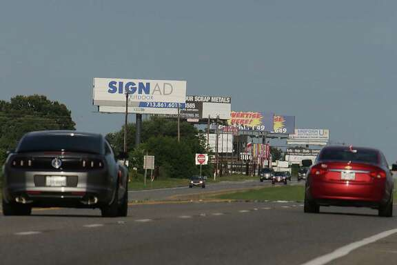 Advertising billboards along US Highway 290 Friday, June 20, 2014, near Hempstead.