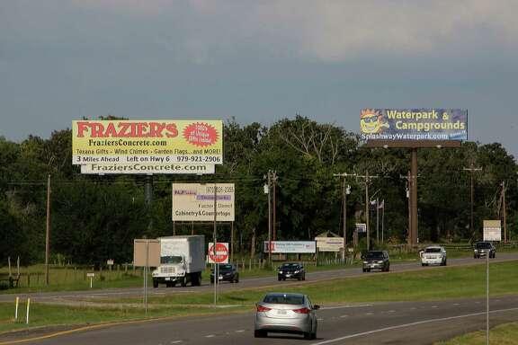 Advertising billboards along US Highway 290 Friday, June 20, 2014, near Hempstead.