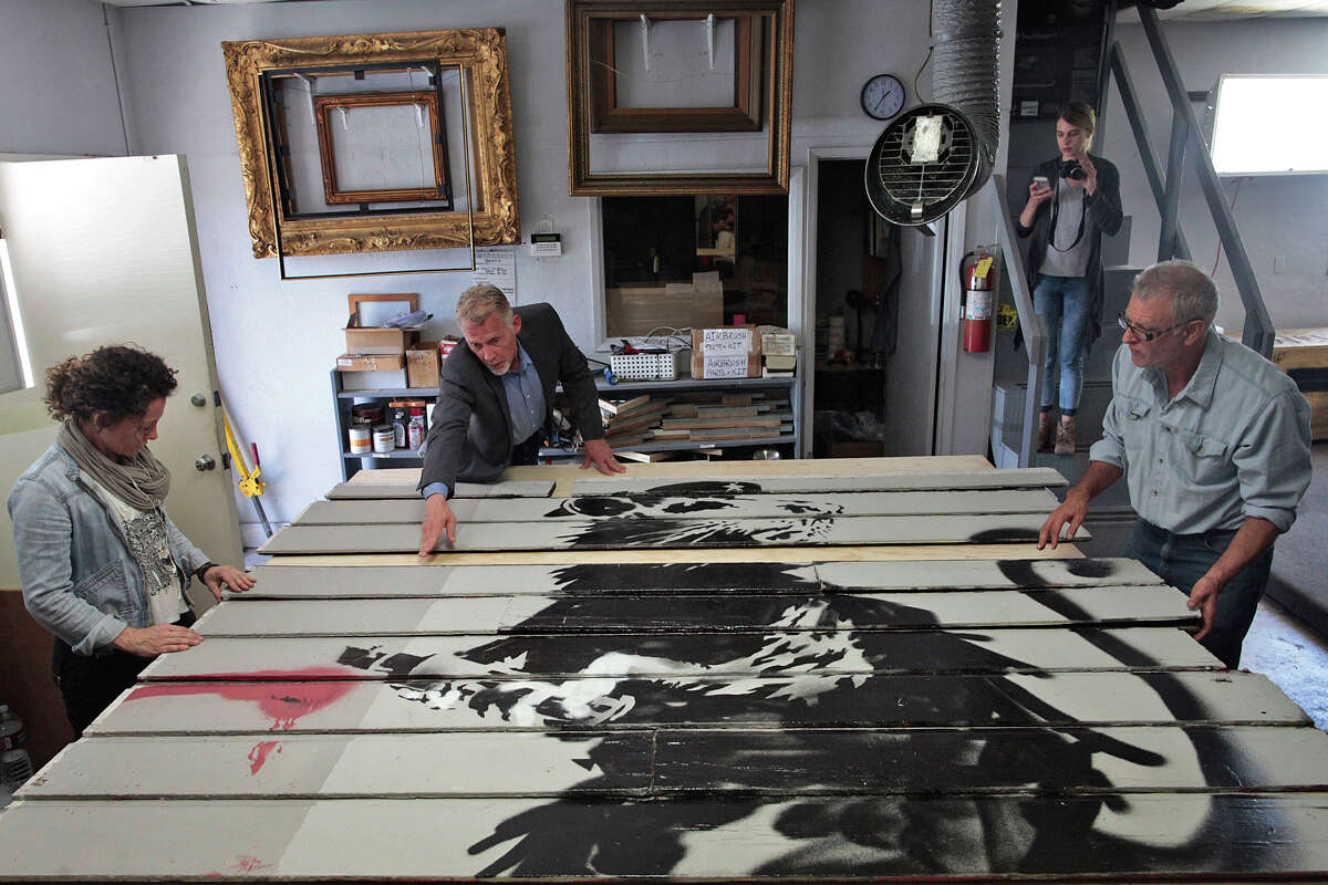 Scott Haskins, second from left, moves slats from a Victorian home featuring a Banksy piece on it in Santa Barbara, Calif. on Tuesday, June 17, 2014. A piece of a Victorian home with Banksy's work on it was taken from San Francisco to Santa Barbara to be framed for display.