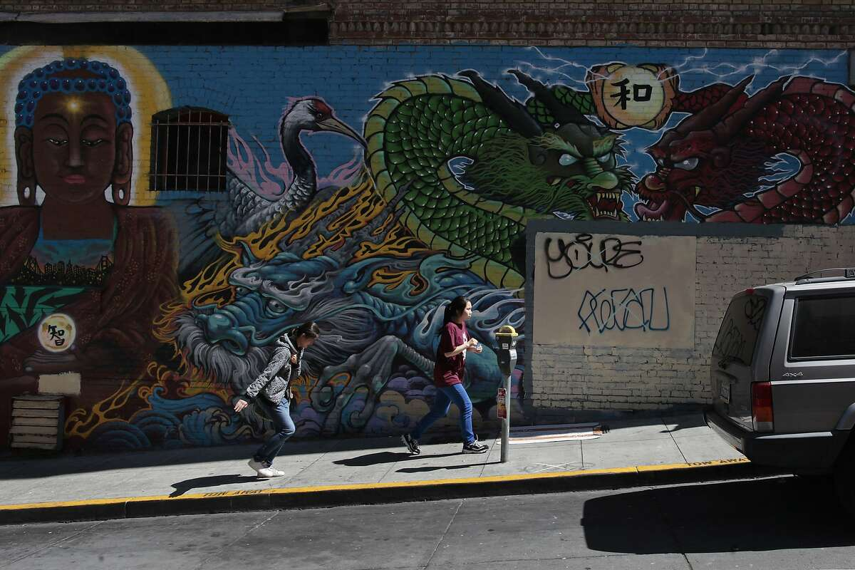 Two women run by a mural that used to have a Banksy piece on it on Commercial St. in San Francisco, Calif. on Thursday, June 19, 2014. San Francisco is home to several Banksy pieces.
