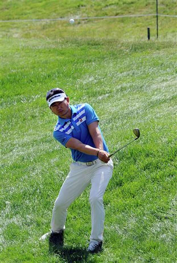 Y.E. Yang, from South Korea, chips to the 18th green during the second round of the Travelers Championship golf tournament in Cromwell, Conn., Friday, June 20, 2014. (AP Photo/Fred Beckham)