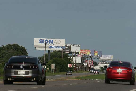 Billboards clutter the side of U.S. 290 near Hempstead. A proposal would raise the maximum height of Texas highway signs to 65 feet, taller than a six-story building.