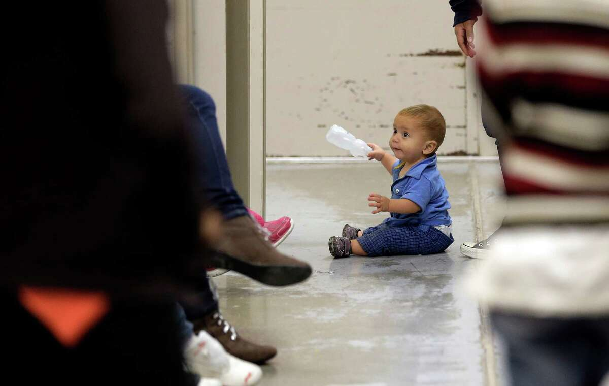 A toddler sits on the floor this week at a U.S. Customs and Border Protection processing facility for detained immigrants in Brownsville, one of two opened for a media tour on Wednesday.