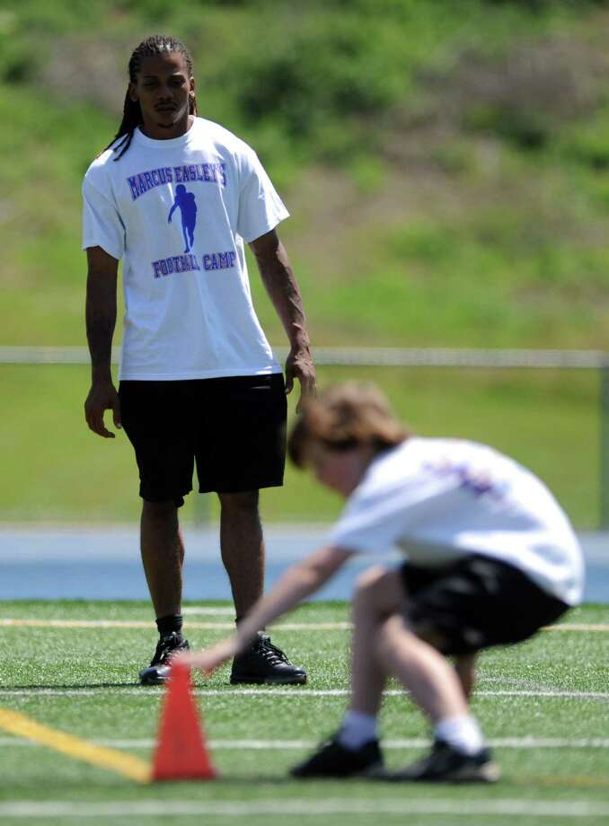 Former Husky Andre Dixon coaches during Marcus Easley's 2nd Annual E.A.S.Y (Excellence, Achievement, Striving, Youthful) Summer Camp, a one-day football camp for children 6-15 years old, at Bunnell High School in Stratford Saturday, June 30, 2012. Photo: Autumn Driscoll / Connecticut Post