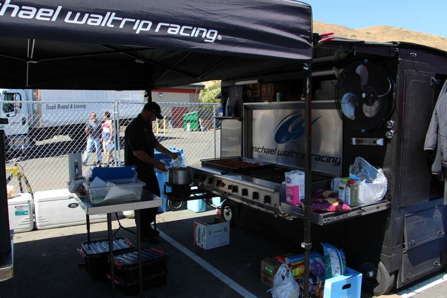 Ed Collins preparing the grill at the Michael Waltrip Racing food tent.