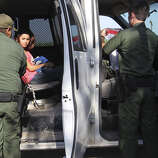 U.S. Border Patrol agents prepare to transport a couple of minor female immigrants in Hidalgo, County southwest of McAllen, Texas, Wednesday, June 11, 2014. A wave of Central American adults with children and unaccompanied minors has overwhelmed U.S. Immigration and Customs detention centers. Immigration officials release some of them on their own recognizance after undergoing processing.