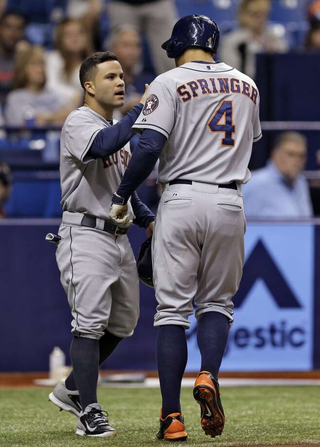 Jose Altuve congratulates George Springer (4) after Springer hit a two-run home run during the third inning. Photo: Chris O'Meara, Associated Press