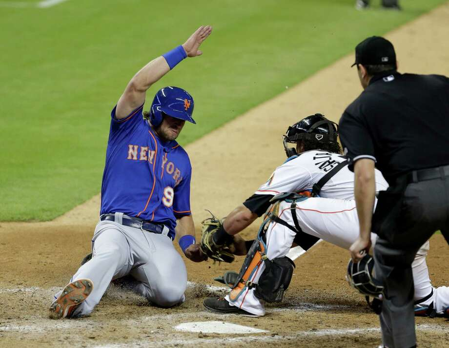 New York Mets' Kirk Nieuwenhuis (9) is tagged out at home plate by Miami Marlins catcher Jarrod Saltalamacchia, center, as Nieuwenhuis tried to score on a fly ball hit by Chris Young in the ninth inning of a baseball game as home plate umpire Lance Barrett, right, watches the play in Miami, Friday, June 20, 2014. The Marlins won 3-2. (AP Photo/Alan Diaz) ORG XMIT: FLAD115 Photo: Alan Diaz / AP
