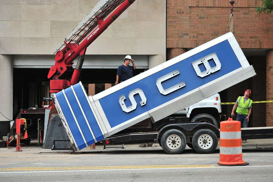 Crews remove a bus depot sign from the Greyhound building in downtown Ann Arbor on Friday, June 20, 2014. The 1940s-era sign is being placed in storage while a new hotel is constructed where the bus depot now stands, and it the sign is expected to be reinstalled on the new building.  Photo: Ryan Stanton, Associated Press