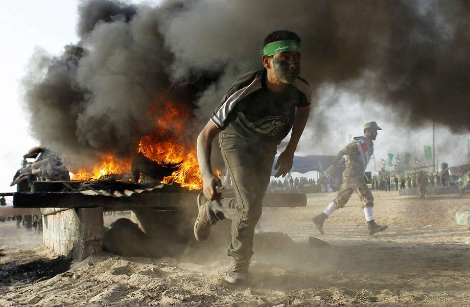 A Palestinian youth runs as he takes part in military-inspired exercises during a summer camp organised by the Islamist movement Hamas on June 19, 2014 in Rafah, southern Gaza Strip. AFP PHOTO/ SAID KHATIBSAID KHATIB/AFP/Getty Images Photo: Said Khatib, AFP/Getty Images