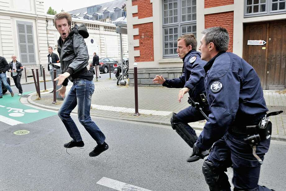 "Policemen chase away a protester during a demonstration of artists and entertainment workers, known as ""intermittents du spectacle"", near the Regional Directorate of Cultural Affairs (DRAC) on June 20, 2014 in Lille, northern France, to protest against the government's plans to reform their status. AFP PHOTO / PHILIPPE HUGUENPHILIPPE HUGUEN/AFP/Getty Images Photo: Philippe Huguen, AFP/Getty Images"