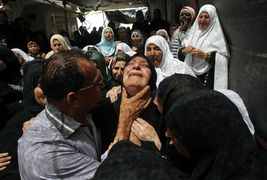 The mother of Mohammed Dudin, a 14-year-old Palestinian shot dead by Israeli troops in overnight clashes in Dura, weeps during his funeral in the Palestinian village, south of the West Bank city of Hebron, on June 20,2014. Palestinian security sources said clashes erupted in Dura after Israeli forces arrived to conduct arrests as part of the operation to locate three Israeli teenagers they believe were abducted by Islamist movement Hamas in the West Bank.  AFP PHOTO/ HAZEM BADERHAZEM BADER/AFP/Getty Images Photo: Hazem Bader, AFP/Getty Images