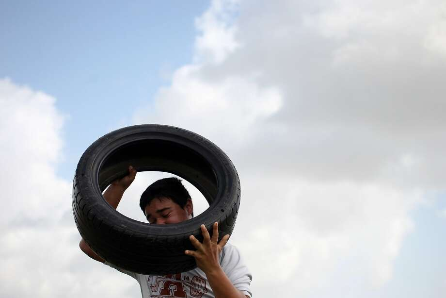 Alice High School junior Levi Lopez tries to keep a tire over his head during the Texas Tough Lineman Challenge at Ray High School, Friday, June 20, 2014, in Corpus Christi, Texas. Twelve teams of lineman from seven different Coastal Bend high schools competed in a series of skill and strength challenges during the event.  Photo: Michael Zamora, Associated Press