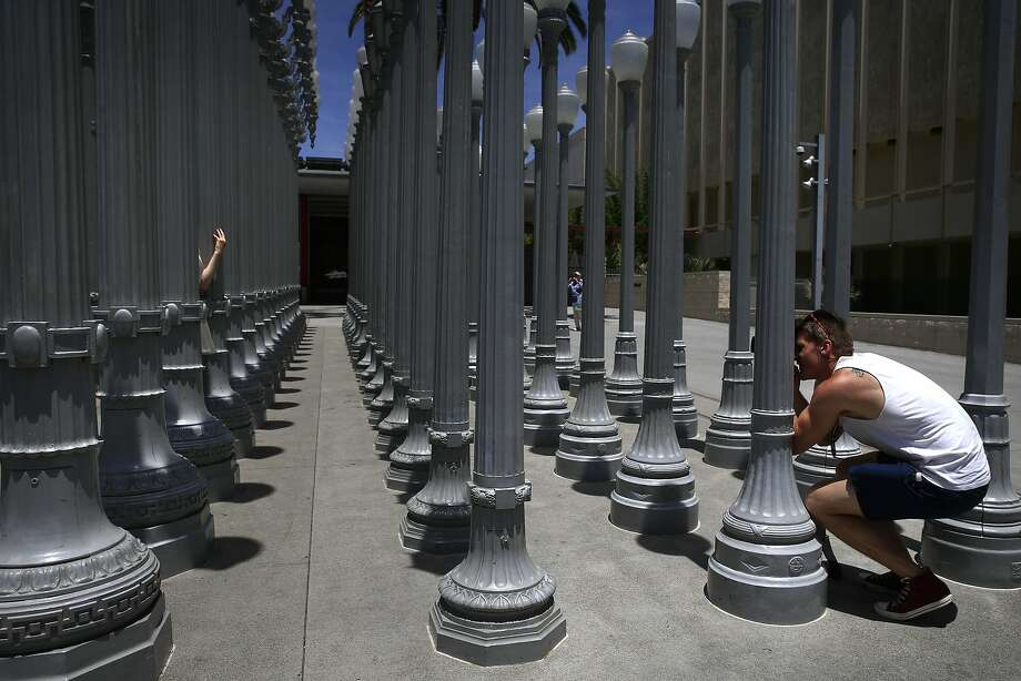 Lamppost labyrinth: Marcus Bergkvist, visiting from Sweden, takes pictures of his girlfriend inside Chris 