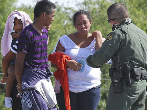 Skyrocketing numbers of immigrants such as these being questioned near McAllen have overburdened U.S. border security. Photo: Jerry Lara / San Antonio Express-News / ©2014 San Antonio Express-News
